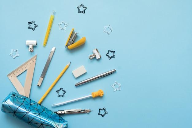 Astuccio per le matite con materiale scolastico su un tavolo di legno blu