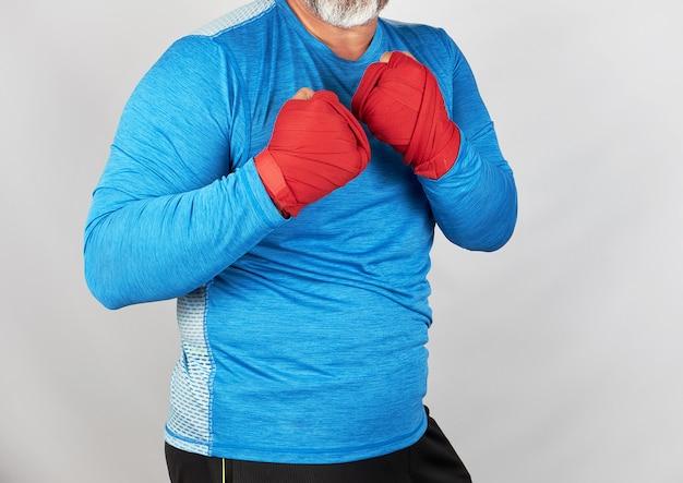 Atleta adulto in abiti blu, mani avvolte in un bendaggio elastico rosso