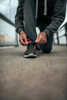 Atleta anziano che lega i lacci delle scarpe.