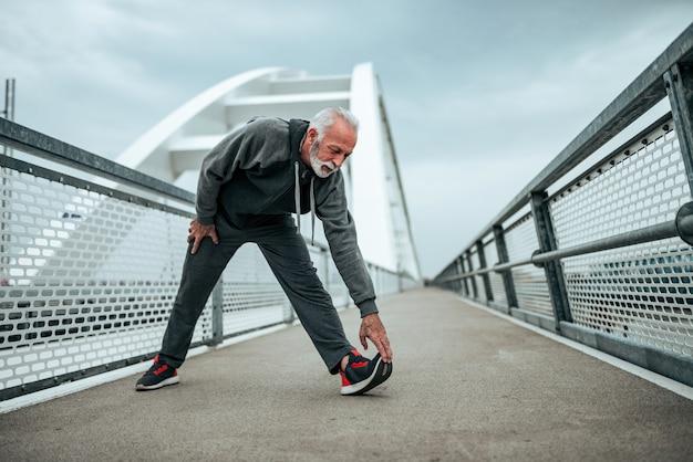 Atleta anziano che si estende all'aperto in città.