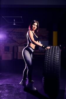 Atleta attraente della donna di medio evo di misura che posa con una gomma enorme in palestra. cross fit donna con grande pneumatico