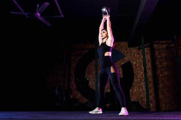 Atleta attraente della donna di misura che esegue un'oscillazione della campana del bollitore in palestra