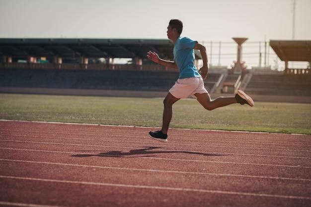 Atleta che corre da solo su una pista da corsa per tutte le stagioni