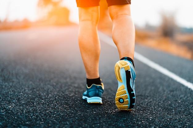 Atleta che esegue i piedi di sport sulla forma fisica di stile di vita sano della traccia