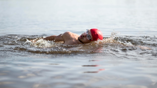Atleta che nuota nel lago