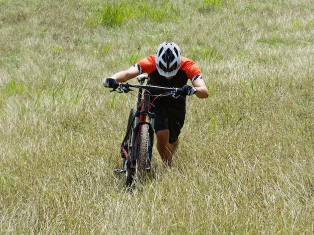 Atleta ciclista arrampicata montagna a piedi.