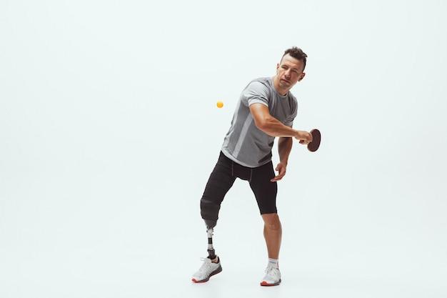 Atleta con disabilità o amputato isolato su bianco. giocatore di tennis maschile professionista con allenamento per protesi delle gambe