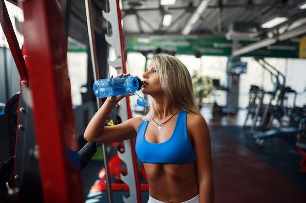 Atleta con una bottiglia d'acqua in palestra