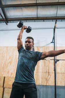 Atleta crossfit facendo esercizio con manubri.