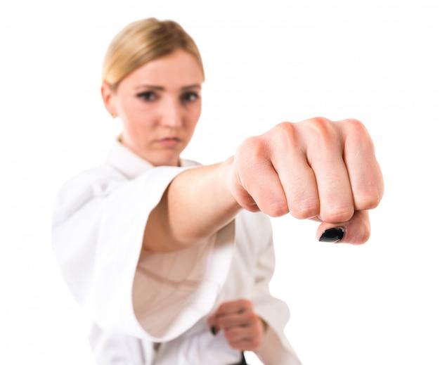 Atleta della donna del primo piano che mostra pugno su bianco