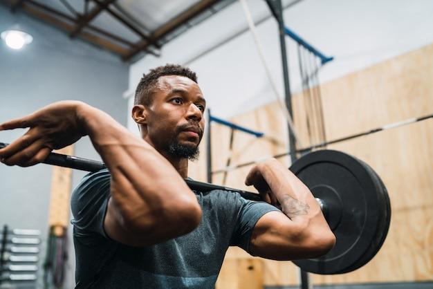 Atleta di crossfit che fa esercizio con un bilanciere.