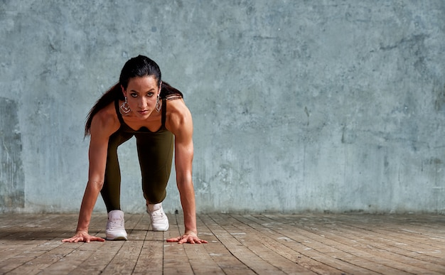 Atleta di fitness all'inizio contro il muro preparando per lo sprint