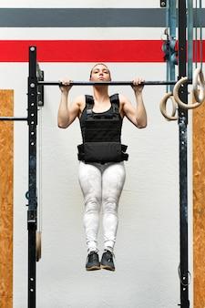 Atleta facendo pull-up ponderati su una barra