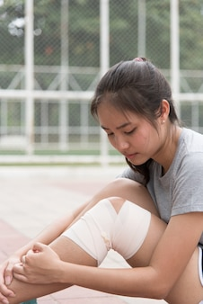 Atleta femminile asiatico che si siede accanto allo stadio ha avuto un infortunio al ginocchio e ha ottenuto il suo primo soccorso.