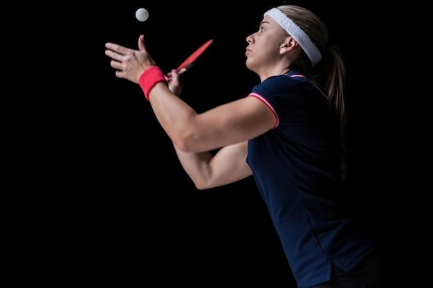 Atleta femminile che gioca ping pong sul nero