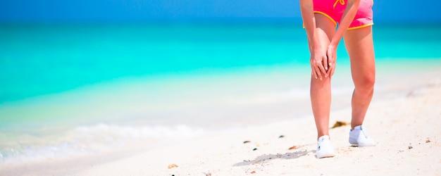 Atleta femminile che soffre di dolore alla gamba mentre si esercita sulla spiaggia bianca