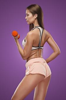 Atleta giovane donna muscolare che propone allo studio su sfondo lilla con manubri