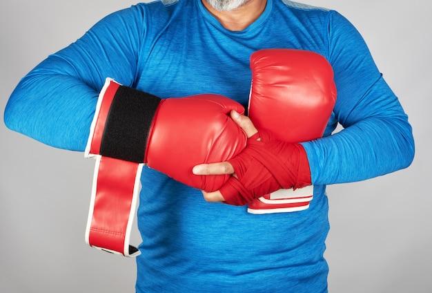 Atleta in abiti blu, le mani sono avvolte da un bendaggio tessile rosso