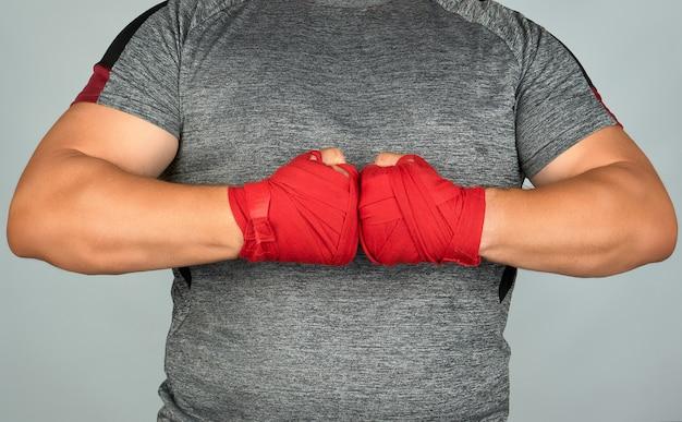 Atleta in abiti grigi si unì alle sue mani davanti al petto