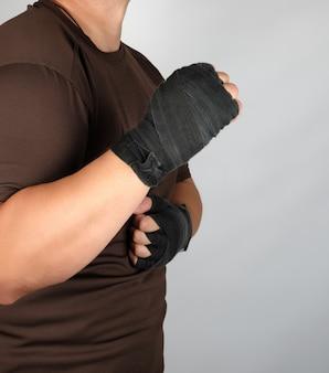 Atleta in abiti marroni con benda sportiva in tessuto nero mani fasciate