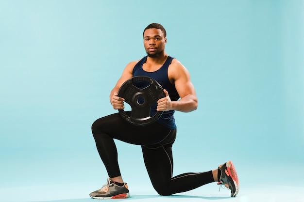 Atleta in attrezzatura della palestra che tiene i pesi