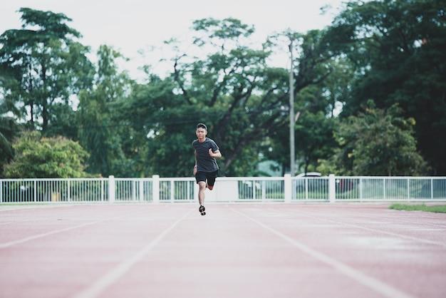 Atleta in piedi su una pista da corsa per tutte le stagioni