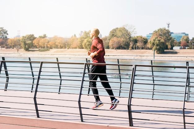Atleta maschio adatto che corre all'aperto per rimanere in buona salute