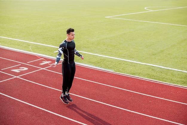Atleta maschio che salta sulla pista di corsa rossa nello stadio