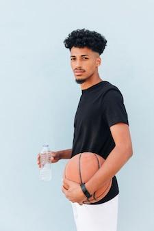 Atleta maschio che sta con la pallacanestro e la bottiglia di plastica su fondo blu molle