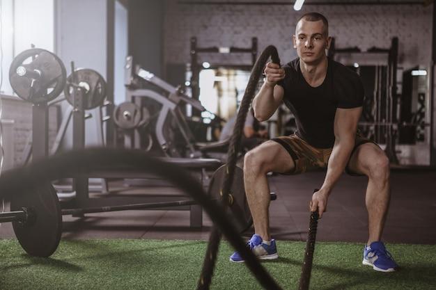 Atleta maschio del crossfit che risolve con le corde di battaglia alla palestra
