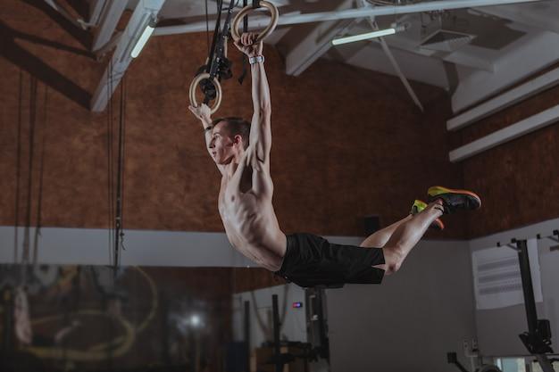 Atleta maschio muscolare del crossfit che risolve sugli anelli relativi alla ginnastica