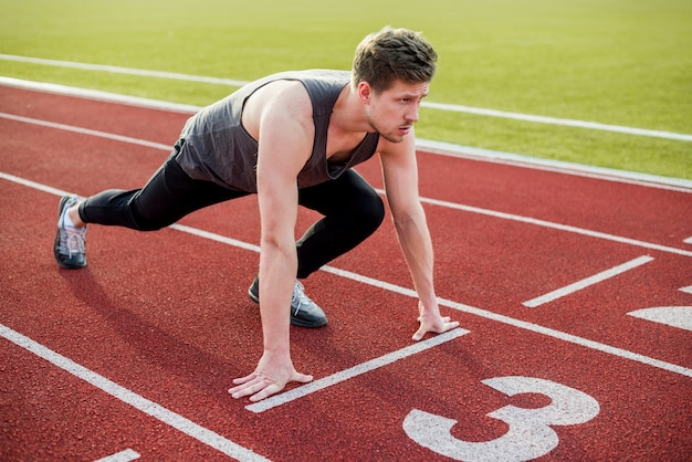 Atleta maschio pronto per iniziare la gara sulla pista di atletica