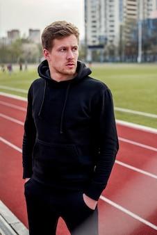 Atleta maschio serio che sta sulla pista con le mani nel suo distogliere lo sguardo della tasca