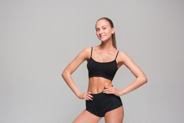 Atleta muscolare della giovane donna che posa sul gray