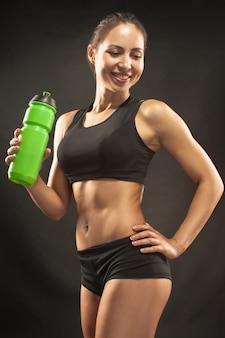 Atleta muscolare della giovane donna con un'acqua sul nero