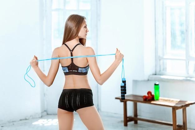 Atleta muscolare della giovane donna con una corda per saltare su bianco