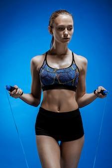 Atleta muscolare della giovane donna con una corda per saltare sul blu