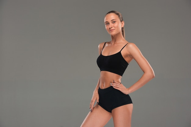 Atleta muscolare della giovane donna su gray