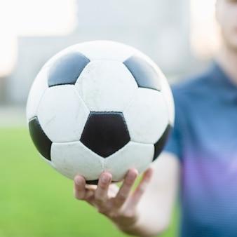 Atleta sfocato che mostra il pallone da calcio