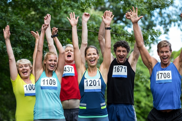 Atleti di maratona in posa con le braccia alzate