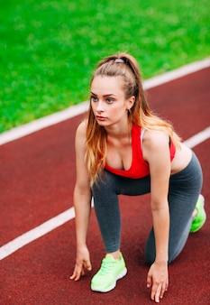 Atletica donna in pista iniziando a correre. concetto di fitness sano con stile di vita attivo.