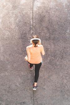 Atletica donna jogging sul marciapiede.