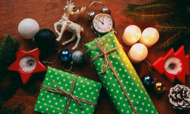Atmosfera di capodanno regalo di capodanno e candelabro accanto all'albero di natale e ai giocattoli di natale