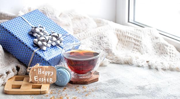 Atmosfera pasquale, accogliente natura morta pasquale con decorazioni vicino alla finestra. tè del mattino con dessert.