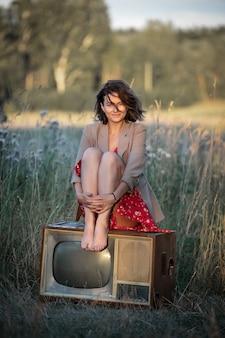 Atmosferico ritratto di una giovane donna in un abito rosso seduto su un vecchio televisore retrò