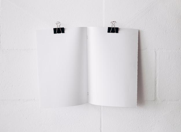 Attaccatura bianca della carta in bianco con le graffette del bulldog su libro bianco contro il contesto bianco della parete