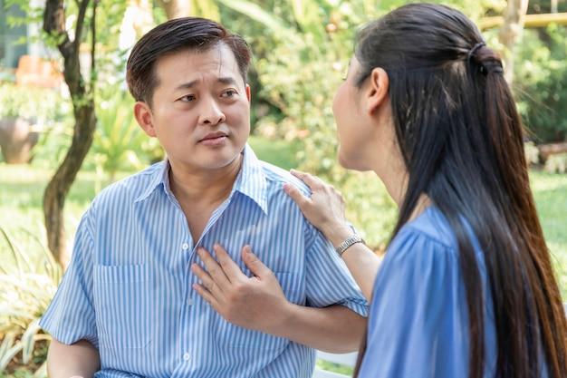 Attacco di cuore asiatico dell'uomo senior durante il rilassamento con la moglie al parco.