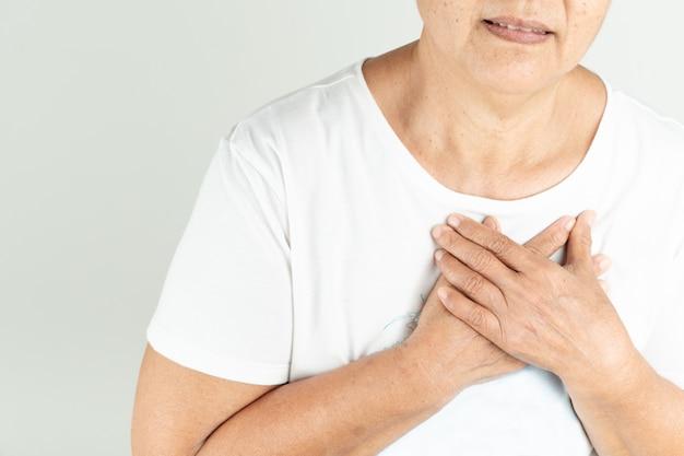 Attacco di cuore della donna anziana che tiene seno