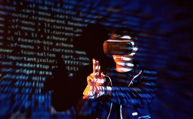 Attacco informatico con hacker incappucciato irriconoscibile utilizzando la realtà virtuale, effetto glitch digitale
