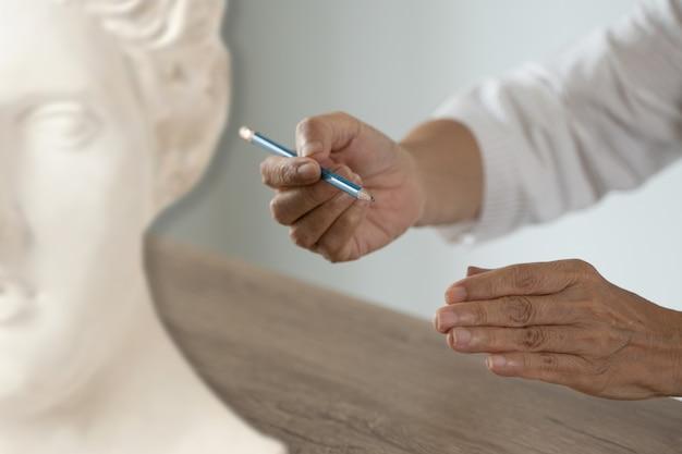 Attenta donna senior arte e scultura divertimento al laboratorio creativo donna pittura